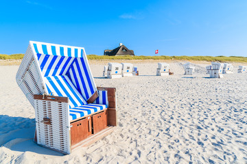Fototapete - Wicker chairs on white sand Kampen beach with typical Frisian house roof in background, Sylt island, North Sea, Germany