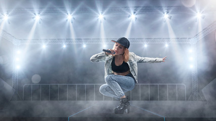 Female singer in casual style performing with lights on background
