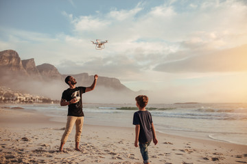 Father and son operating drone by remote control at beach Wall mural