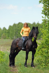 Woman walking horse in forest