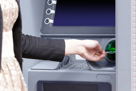 Close up hand inserting card into ATM