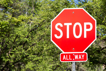 Stop sign against green leaves