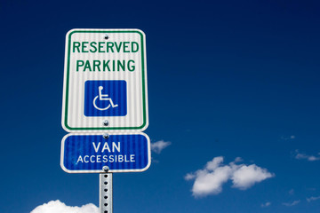 Reserved Handicapped Parking Sign with sky and clouds