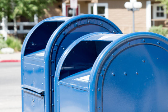 Two blue roadside mailboxes