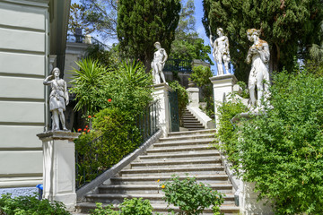 Classical inspired statues on stairs to the Achilleion palace in Gastouri, Corfu island in Greece.