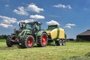 Ernte - Traktor mit Großballenpresse vor blauem Himmel