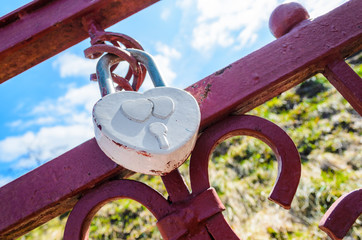 A white heart-shaped love padlock locked to a bridge by newlyweds to symbolize their love