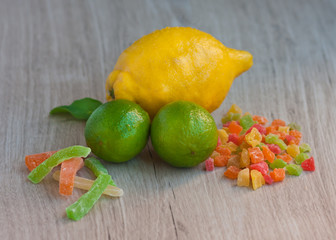 A big yellow lemon, two ripe fresh limes, some candied fruit. Tea ceremony. Dessert. Fresh and dried fruits