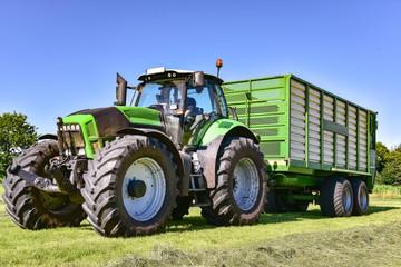 Ernte - Landtechnik - Einfahren der Grassilage mit Traktor und Ladewagen