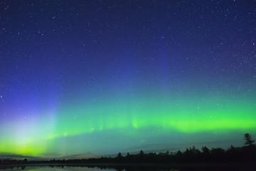 Northern lights arching across the silhouetted night landscape, large expanse of stars