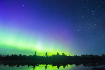 Bright colors of the northern lights arching over silhouetted wilderness landscape