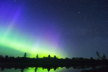 Northern lights vibrant in night sky full of stars and faint milky way