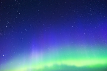 Deep blue night sky full of bright stars, colorful northern lights glowing
