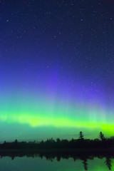Vertical composition of northern lights and deep blue starry night sky