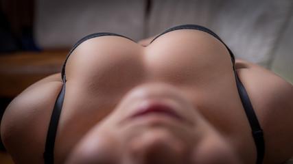 Closeup of a female sexy big breasts in a black bra