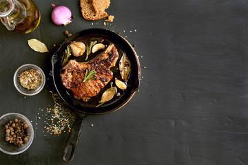 Pork steak in frying pan, top view