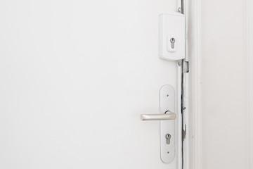 door handle and bar lock on white apartment door
