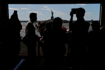People take photos of the Statue of Liberty from the Staten Island Ferry between Staten Island and Manhattan in New York City