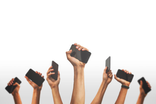 group of people's hands holding phones and rising them up against a white backgroud