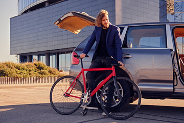 A man holds fixed bicycle near the car with open trunk.