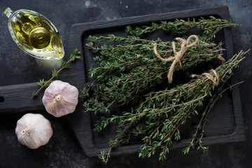 Above view of a black wooden serving tray with bunches of fresh thyme, garlic and olive oil, studio shot