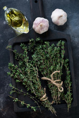 Bunches of fresh thyme on a black wooden serving board, view from above, vertical shot