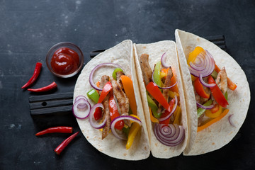 Tortillas filled with freshly made tex-mex pork fajitas. High angle view over dark metal background