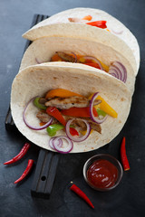Mexican pork fajitas served in wheat wraps, selective focus, vertical shot
