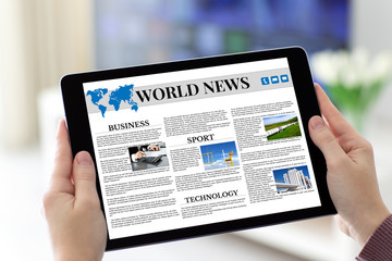 Female hands holding tablet with app world news on screen