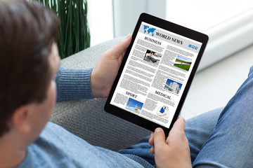 man in jeans holding tablet computer with app world news