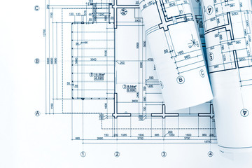 architect workplace with rolls of blueprints and technical drawings