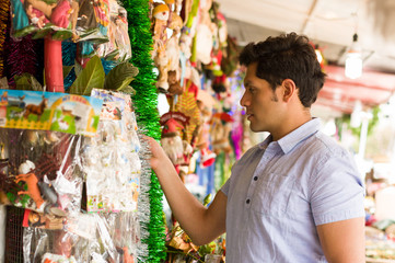 Handsome young man watching beautiful and colorful christmas tree decoration in a market