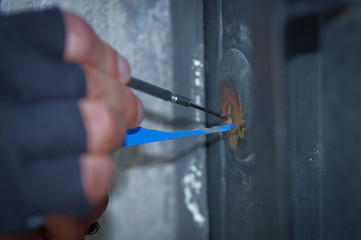 Close up of a burglar holding Lock-picker to open a housedoor