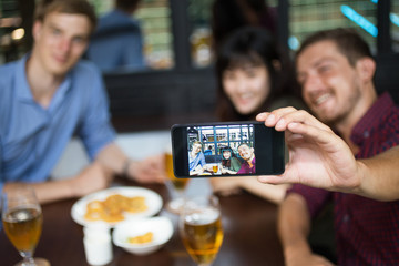 Three Friends Taking Selfie Photo in Pub