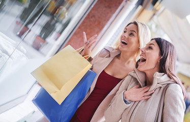 Happy young women enjoying in shopping. Consumerism, fashion, lifestyle concept