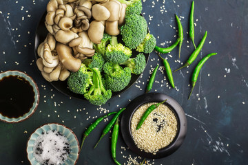 Ingredients for Asian style dinner. Oyster mushrooms, broccoli, soy sauce, white sesame on a dark blue marble background. Top view. The concept of healthy healthy food, vegetarianism, raw food.