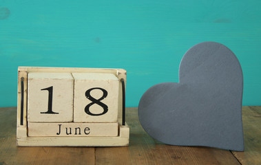 Wooden vintage calendar 18th of june next to wooden heart