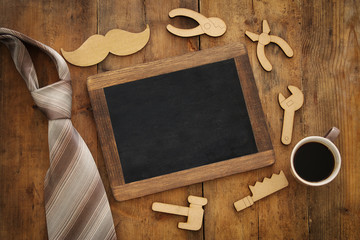 top view image of fathers day composition with wooden shape tools, necktie , cup of coffee and blackboard