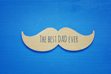 Blue wooden background and paper mustache. fathers day concept