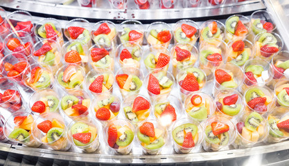 Fruit salad arranged in plastic cups for sale. refrigerator showcase or buffet. Used in cocktails and as a topping to the chocolate fountain. Selective focus