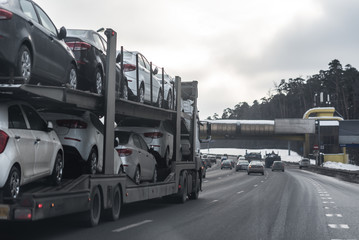 The trailer transports cars on highway.