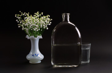 May-lily in a vase, a bottle and a glass of water