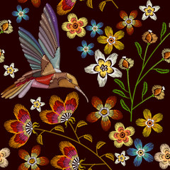 Humming bird and flowers embroidery seamless pattern. Beautiful hummingbirds and spring flowers embroidery on black background. Template for clothes, textiles, t-shirt design