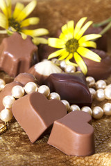 Assortment of chocolate bonbons and pearl necklace on golden background and flowers