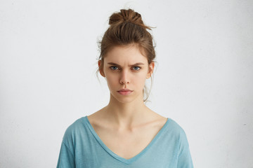 Portrait of outraged young woman with oval face, blue eyes and hair bun wearing blue casual sweater frowning her eyebrows being displeased with something. Scowling pretty female isolated over white