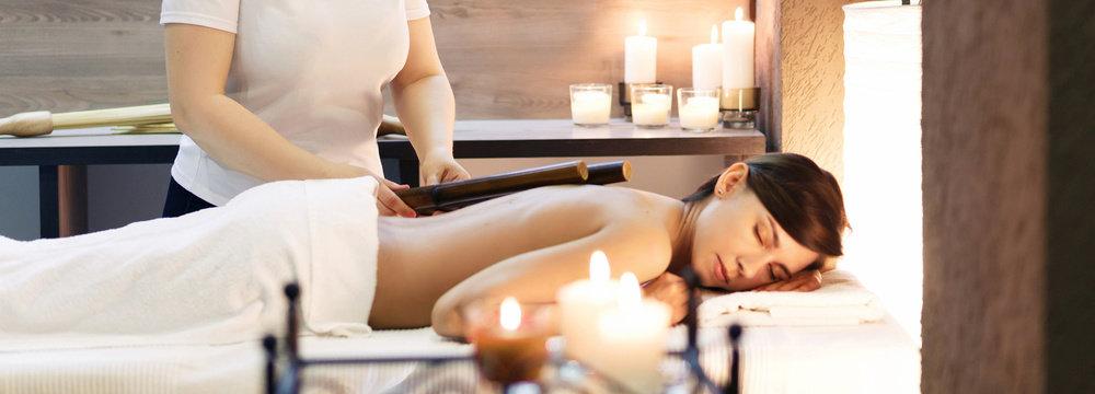 oman having bamboo stick massage at day spa