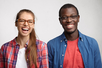 Interracial friends standing shoulder to shoulder having sincere smile and emotions. Young couple posing in studio with pleasant emotions. Caucasian woman with glasses and dark-skinned man smiling
