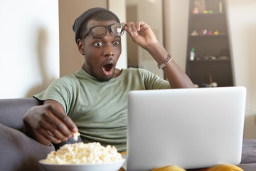 Horrified Afro American man dressed casually sitting at home watching horror films on computer eatting popcorn being scared putting off spectacles looking with wide opened eyes and mouth into screen