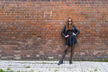 Girl with long hair near an old brick wall