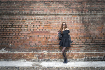 Girl with long hair near an old brick wall
